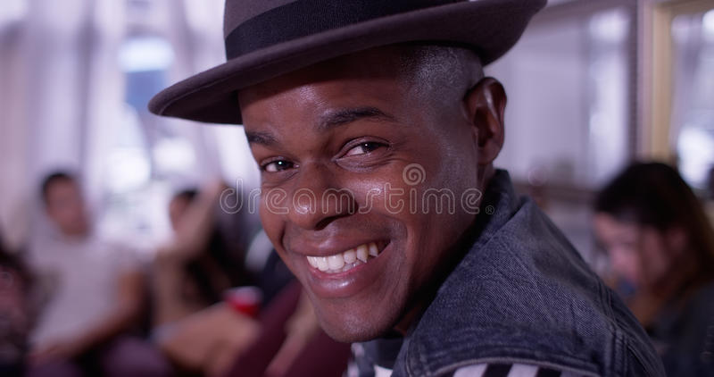 Portrait of Handsome young black hipster man smiling and laughing with group of friends partying in background royalty free stock images