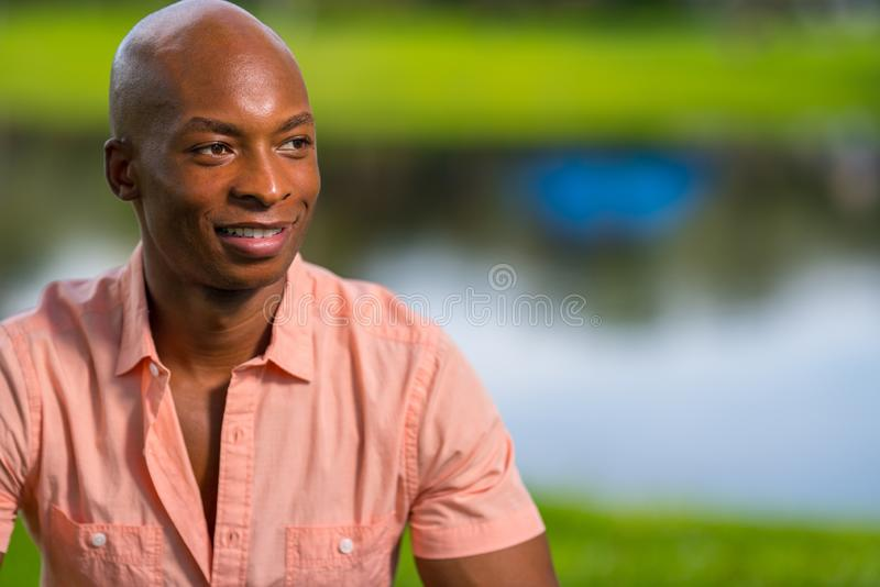 Portrait handsome young black man posing in a park setting. pleasing bokeh lake scene in the background stock photography
