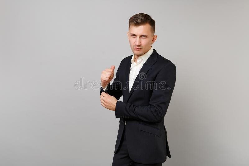 Portrait of handsome young business man in classic black suit, shirt straightening sleeves, cuffs isolated on grey stock images
