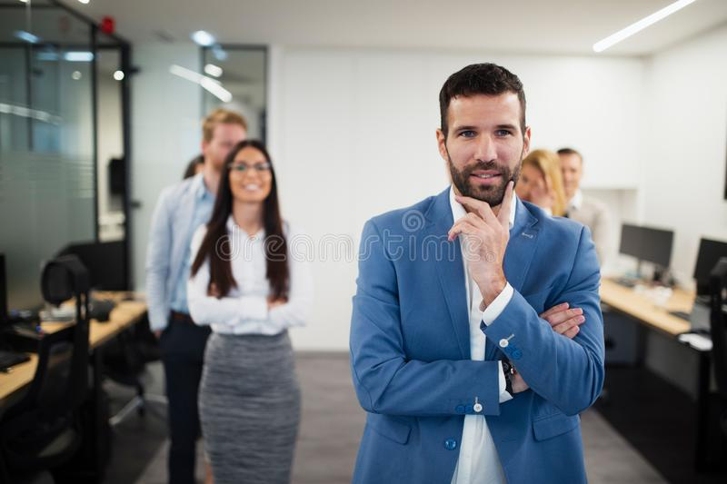 Portrait of handsome young businessman with his colleagues stock photo