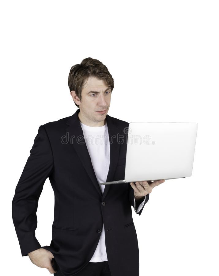 Portrait of handsome young businessman standing holding laptop computer and checking email stock photos