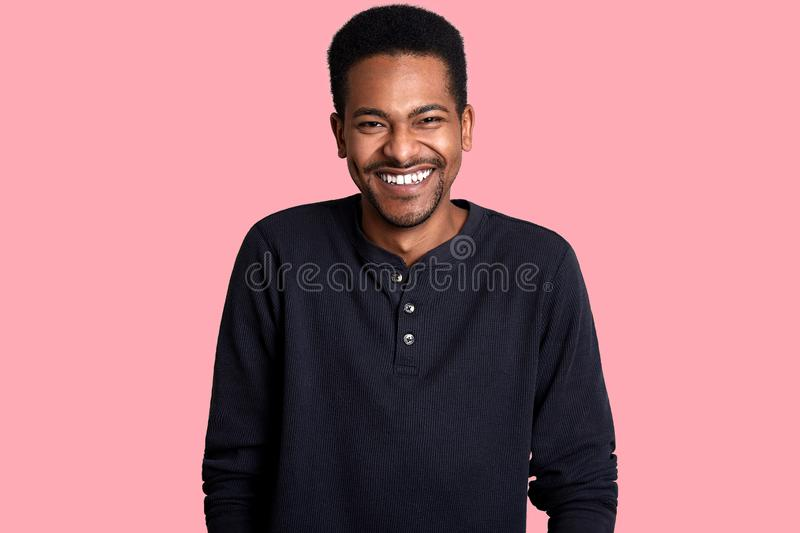 Portrait of handsome young dark skinned man. Good looking laughing male poses in studio, guy hears funny joke. Cheerful boy stands royalty free stock photo