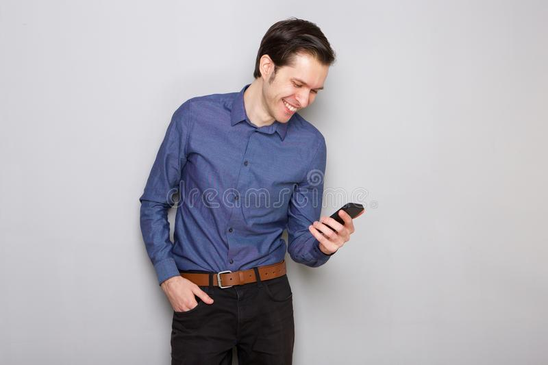Handsome young entrepreneur looking at mobile phone. Portrait of handsome young entrepreneur looking at mobile phone stock photo