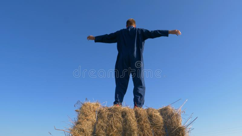 Portrait of a handsome young farmer student sitting on haystack, beautiful smile, in work clothes with airplane in hand. Concept royalty free stock photos