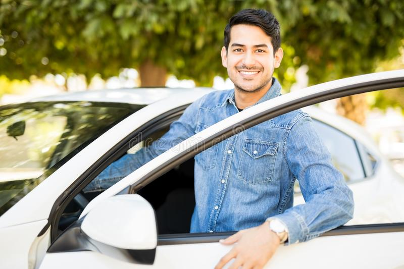Man getting in car. Portrait of handsome young latin man getting inside his car, making an eye contact and smiling royalty free stock photography