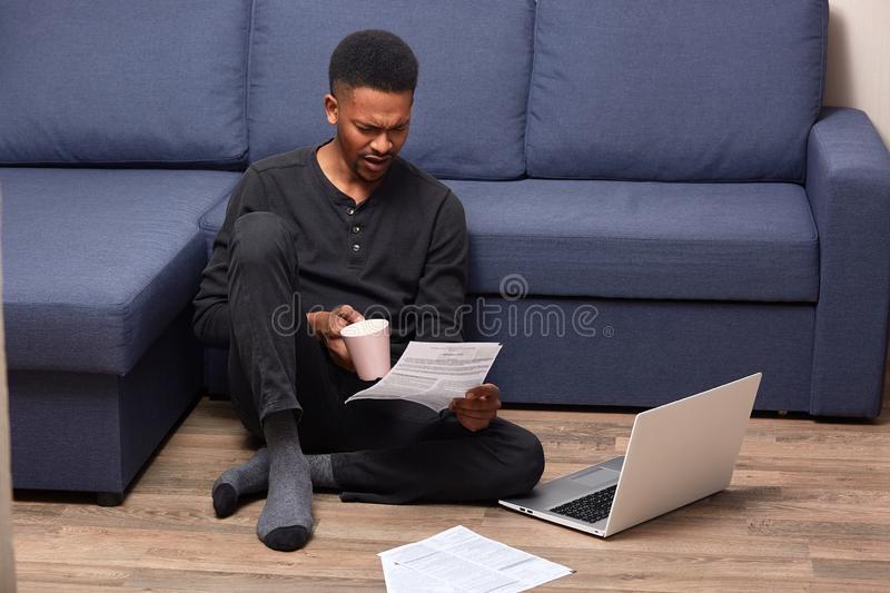 Portrait of handsome young man in black casual outfit, sitting on floor with laptop computer, working with papers and drinking royalty free stock image