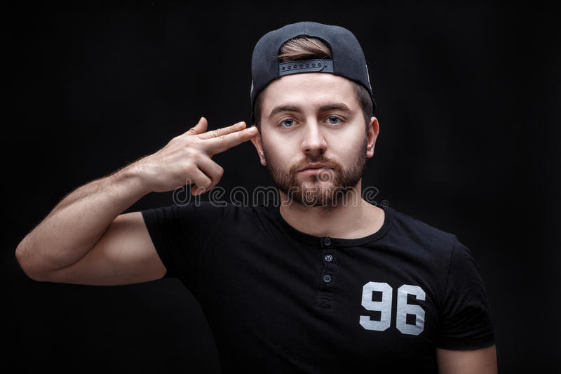 Portrait of handsome young man in black shirt and cap on black background. rapper. Portrait of a handsome young brunette man in a black shirt and cap on a black royalty free stock image