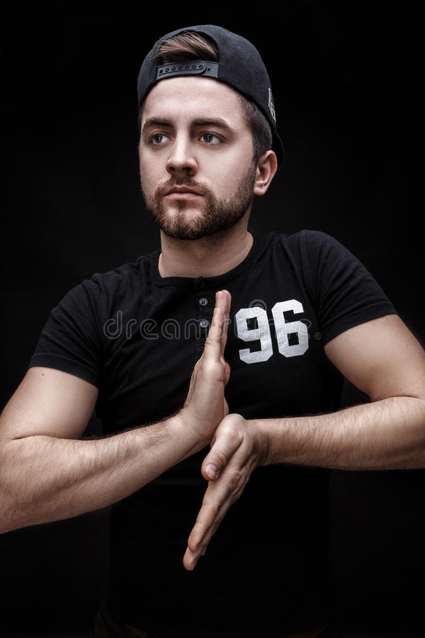 Portrait of handsome young man in black shirt and cap on black background. rapper. Portrait of a handsome young brunette man in a black shirt and cap on a black royalty free stock images