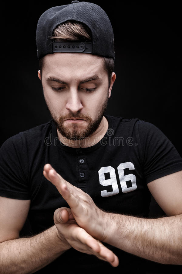 Portrait of handsome young man in black shirt and cap on black background. rapper. Portrait of a handsome young brunette man in a black shirt and cap on a black royalty free stock photos