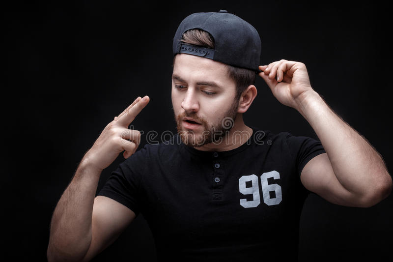 Portrait of handsome young man in black shirt and cap on black background. rapper. Portrait of a handsome young brunette man in a black shirt and cap on a black stock image