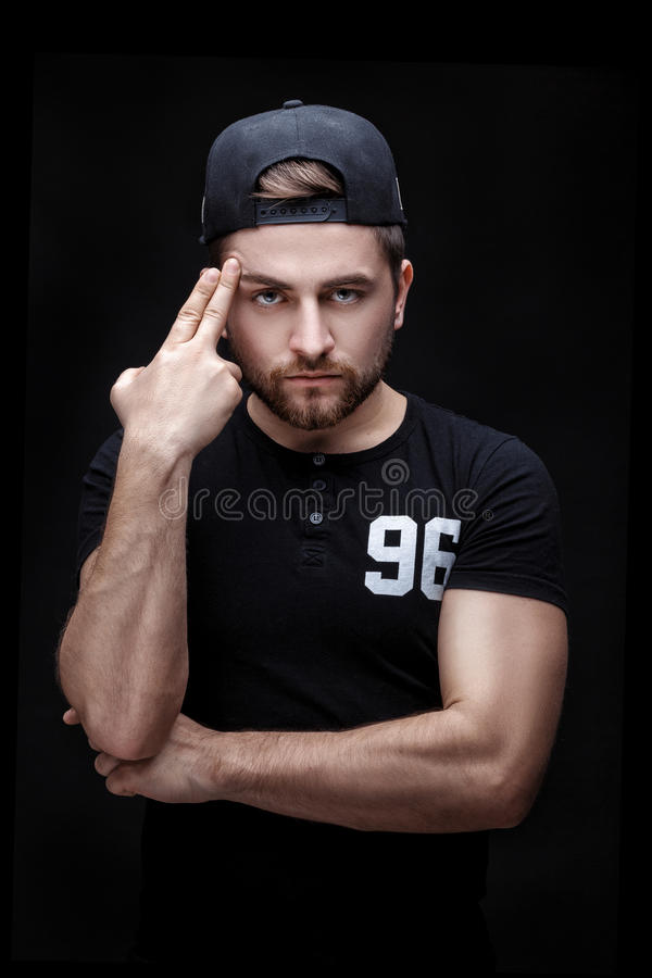 Portrait of handsome young man in black shirt and cap on black background. rapper. Portrait of a handsome young brunette man in a black shirt and cap on a black stock photography