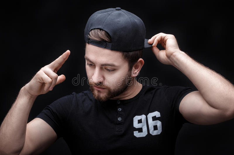 Portrait of handsome young man in black shirt and cap on black background. rapper. Portrait of a handsome young brunette man in a black shirt and cap on a black stock photo