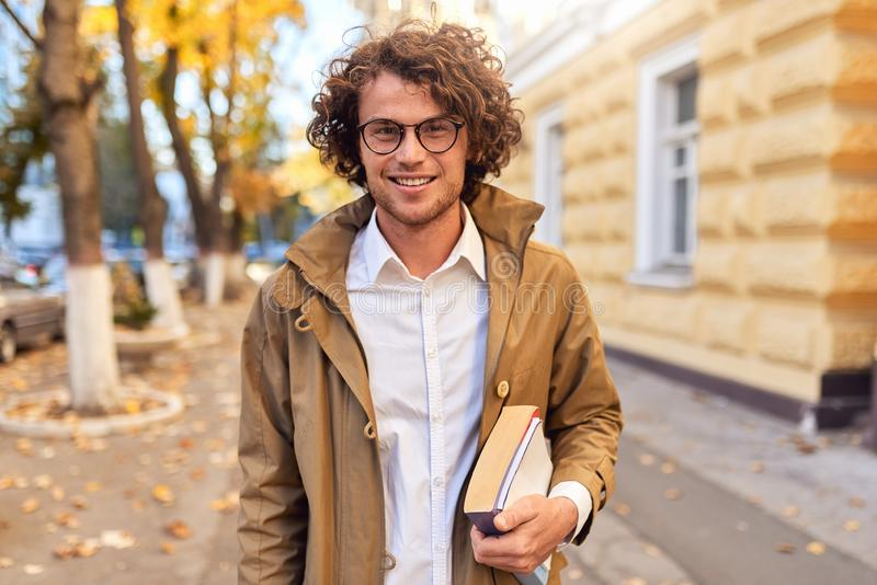 Portrait of handsome young man with books outdoors. College male student carrying books in college campus in autumn street. Background. Smiling guy with glasses royalty free stock photography