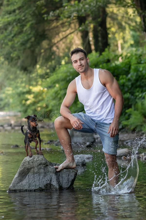Portrait of handsome young man with dog, outdoor stock photos