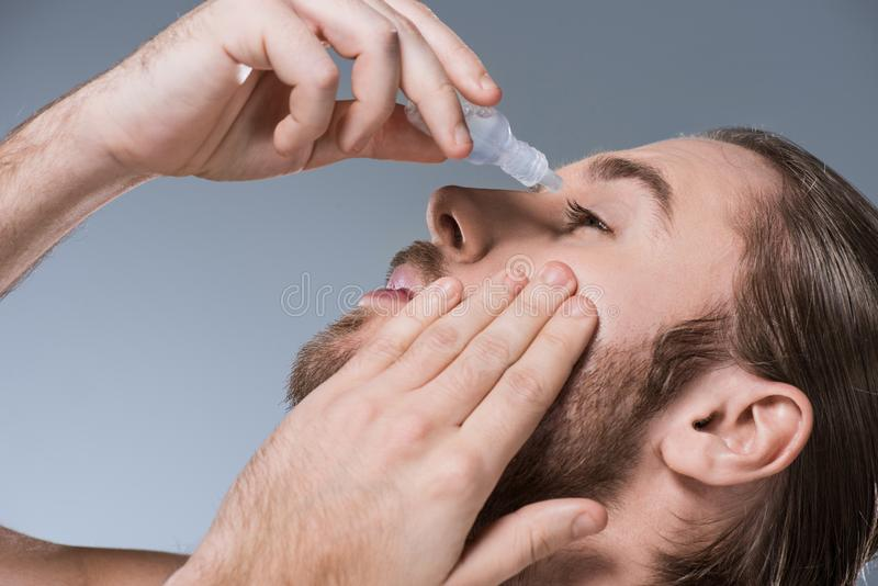 Portrait of handsome young man dripping eye drops with hand on cheek, royalty free stock photos