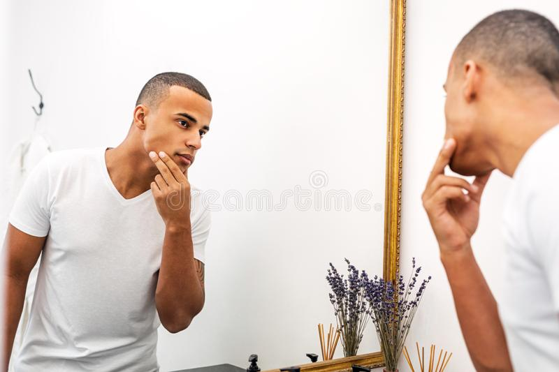 Portrait of a handsome young man examining his face royalty free stock image