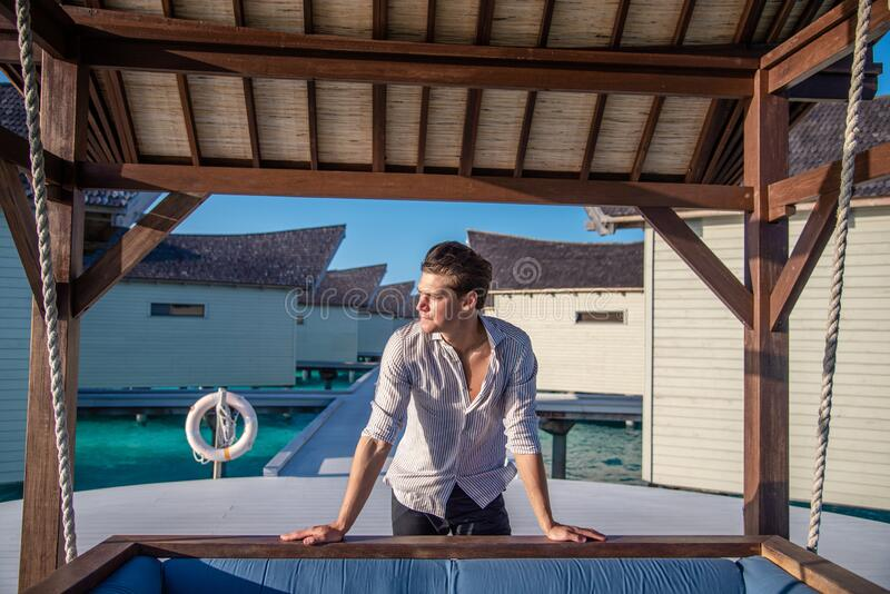 Portrait of handsome young man in expensive shirt near the swing and water villas at the tropical island luxury resort. In Maldives royalty free stock image