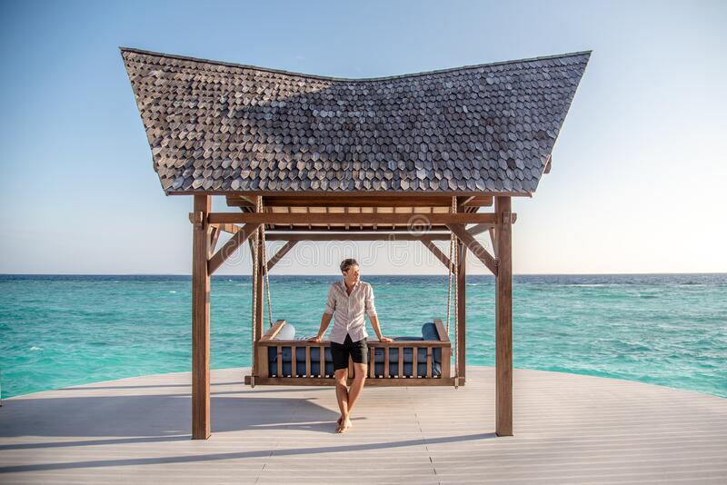 Portrait of handsome young man in expensive shirt standing  near the swing and water villas at the tropical island luxury resort. Portrait of handsome young man royalty free stock image