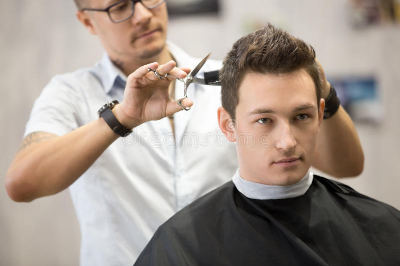 Portrait of handsome young man getting haircut stock photography