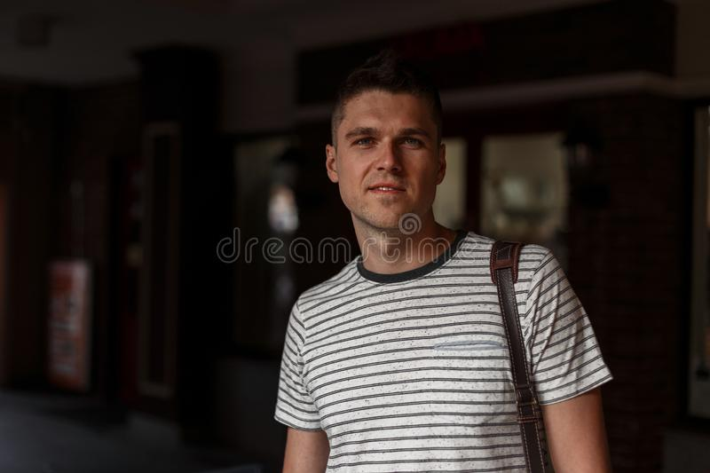 Portrait of a handsome young man with gray eyes with a stylish haircut in a fashionable striped T-shirt with a leather bag royalty free stock photos