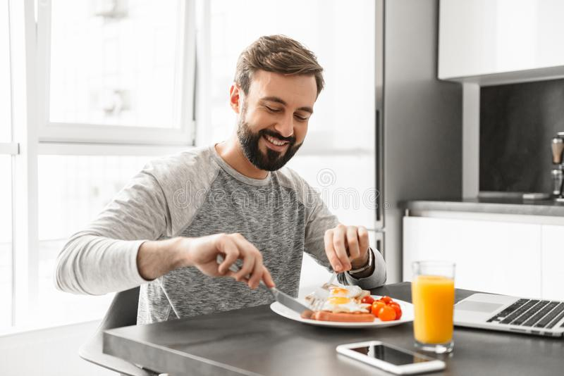Portrait of a handsome young man having breakfast stock image