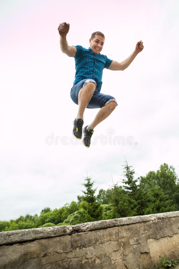 Portrait of handsome young man jumping against the sky stock image