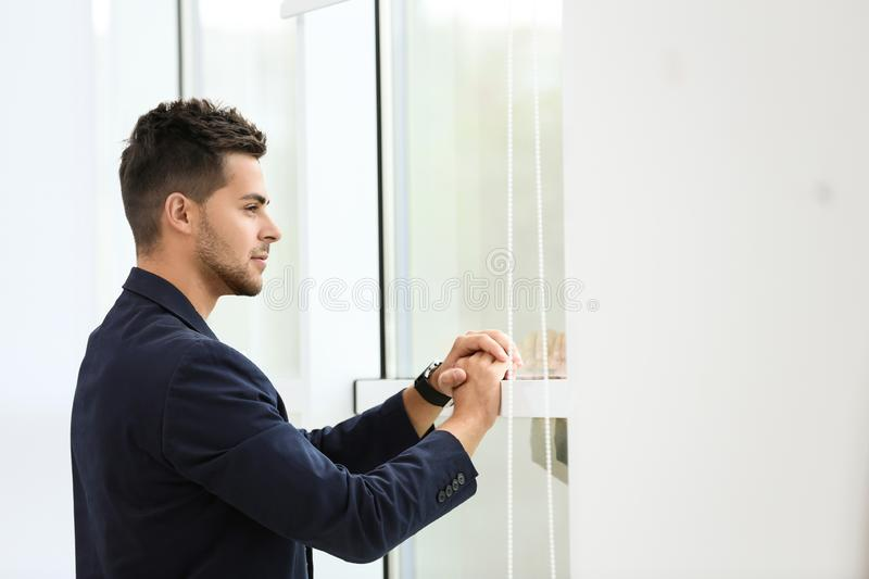 Portrait of handsome young man looking out window stock images