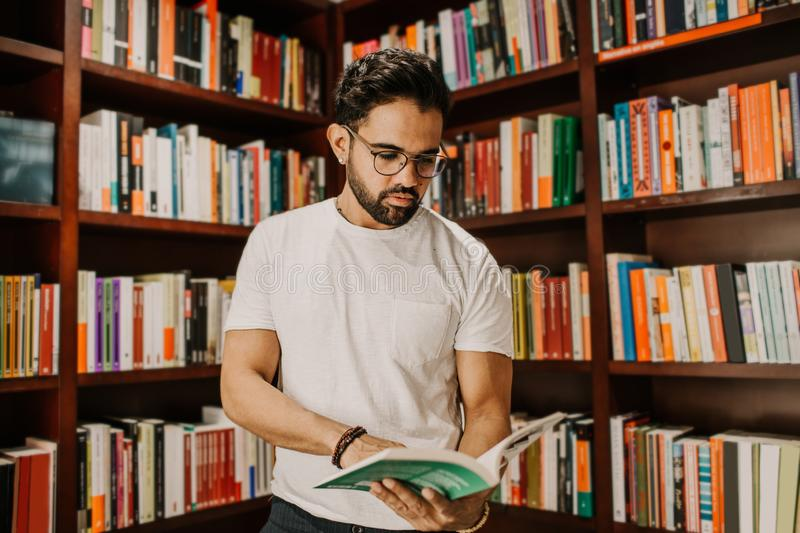Portrait of handsome young man reading book at library. Knowledge and education concept stock image