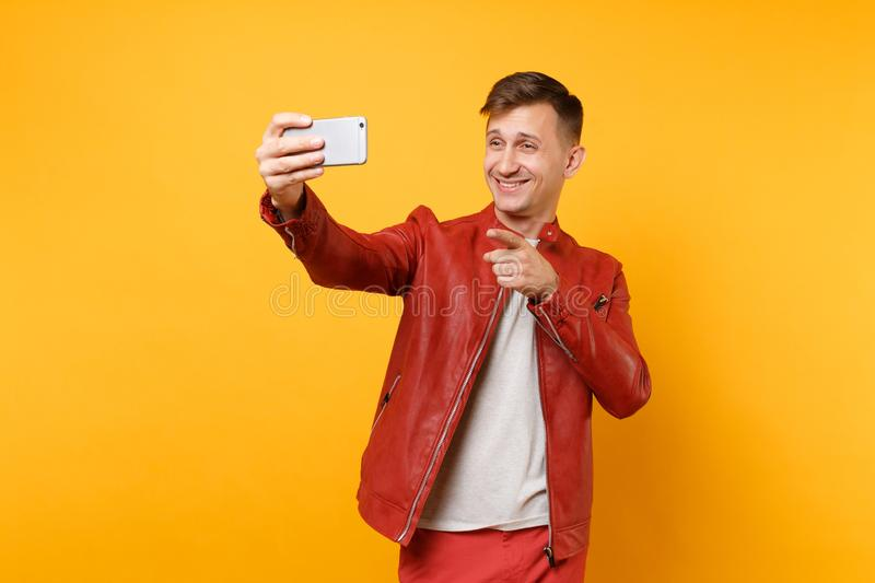 Portrait vogue handsome young man in red leather jacket, t-shirt doing selfie on mobile phone isolated on bright royalty free stock photo