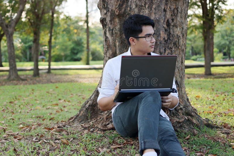 Portrait of handsome young man sitting on a green grass with laptop in the park. stock photos