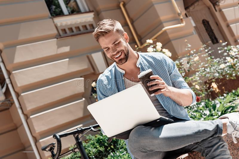The key to success is action. Young smiling man sitting in the park, holding his laptop and a cup of coffee. His bike stock photography