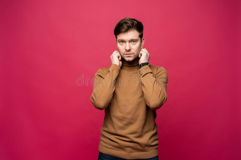 Portrait of a handsome young man smiling against pink background. royalty free stock photo
