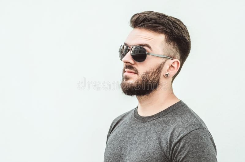 Portrait of a handsome young man standing against gray background. Youth culture. Barbershop stock photos