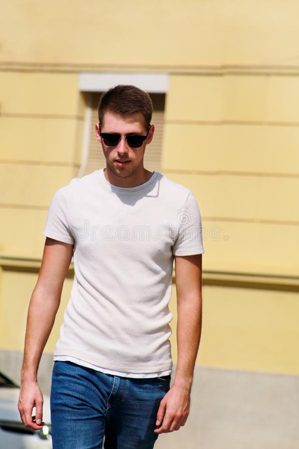 Portrait of handsome young man with sunglasses is posing and walking on urban city street. Male model photo-shoot outdoors. royalty free stock photography