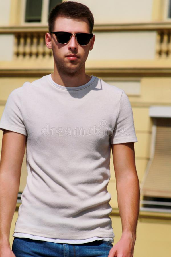 Portrait of handsome young man with sunglasses is posing and walking on urban city street. Male model photo-shoot outdoors. stock photo