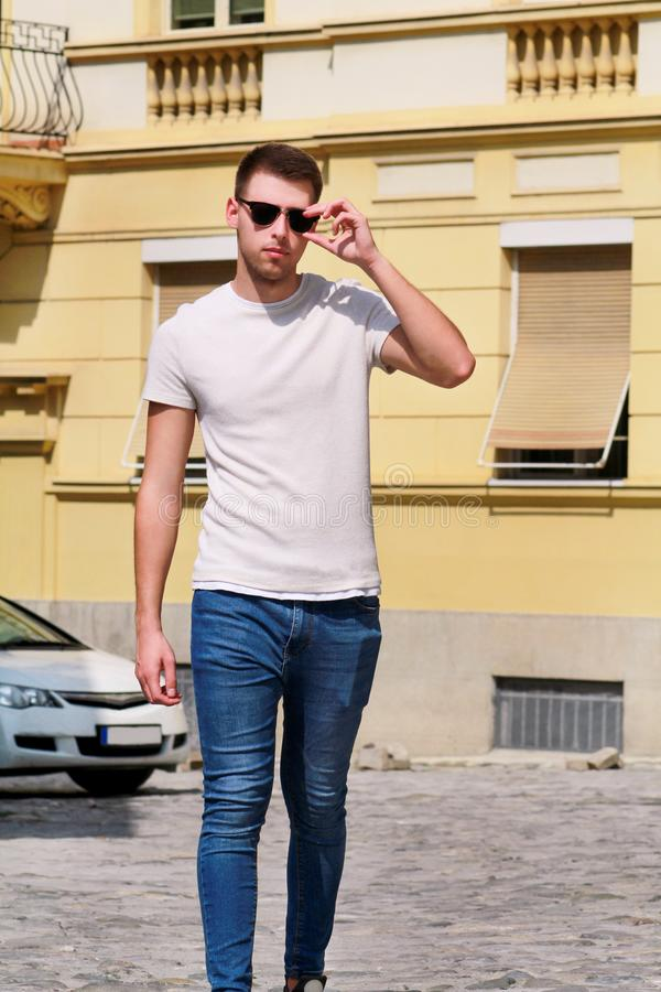 Portrait of handsome young man with sunglasses is posing and walking on urban city street. Male model photo-shoot outdoors. royalty free stock image