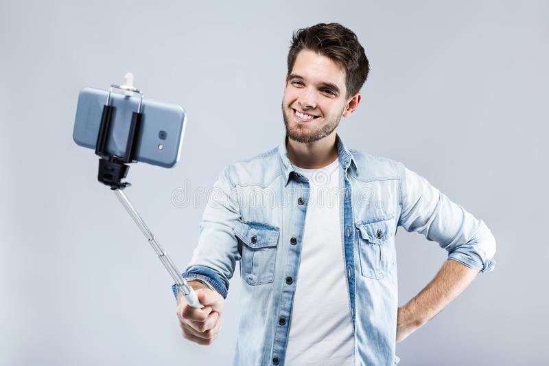 Handsome young man taking a selfie over gray background. stock image