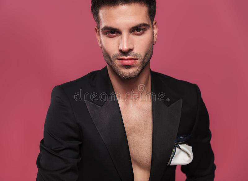 Portrait of handsome young man wearing an undone black tuxedo royalty free stock photos