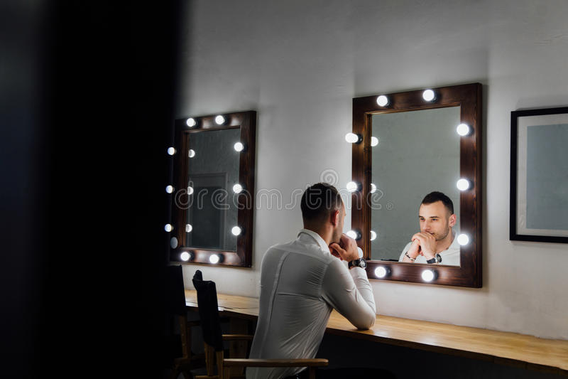 Portrait of handsome young man in white shirt looking into the mirror. stock image