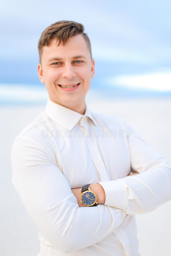 Portrait of handsome young man in white steppe background, wearing shirt. royalty free stock image