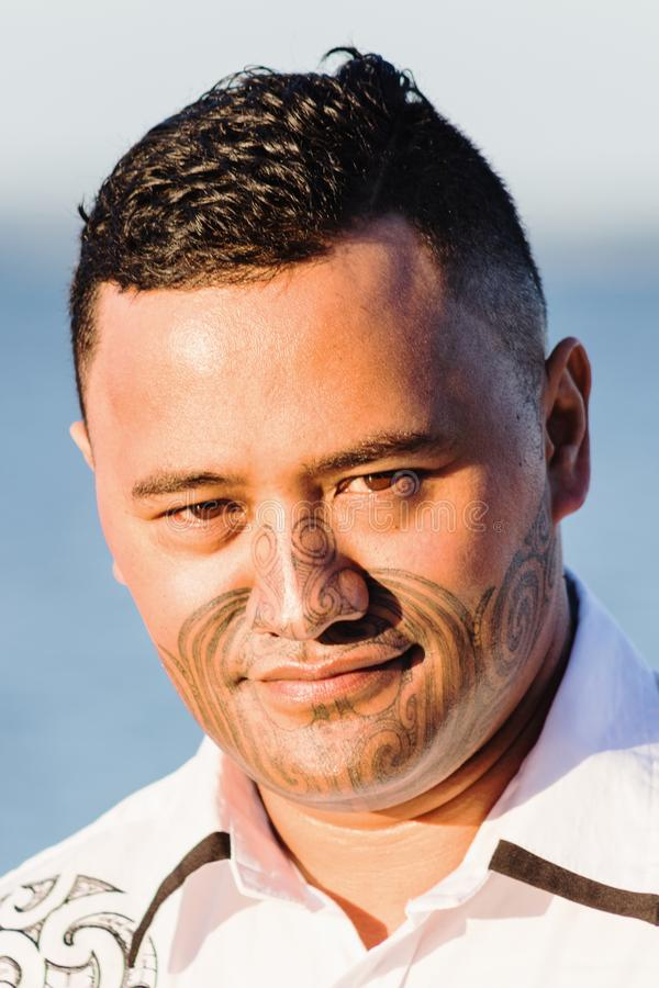 Portrait of a handsome young Maori Man. With traditional face tattooing stock photography