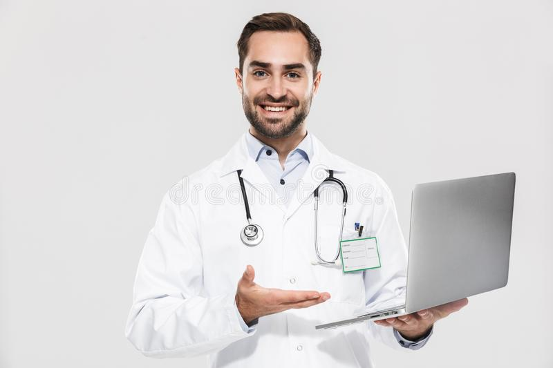 Portrait of handsome young medical doctor with stethoscope working in clinic and holding laptop royalty free stock photos