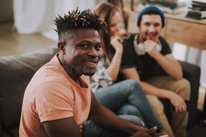 Joyful afro american guy spending time with friends at home stock photography