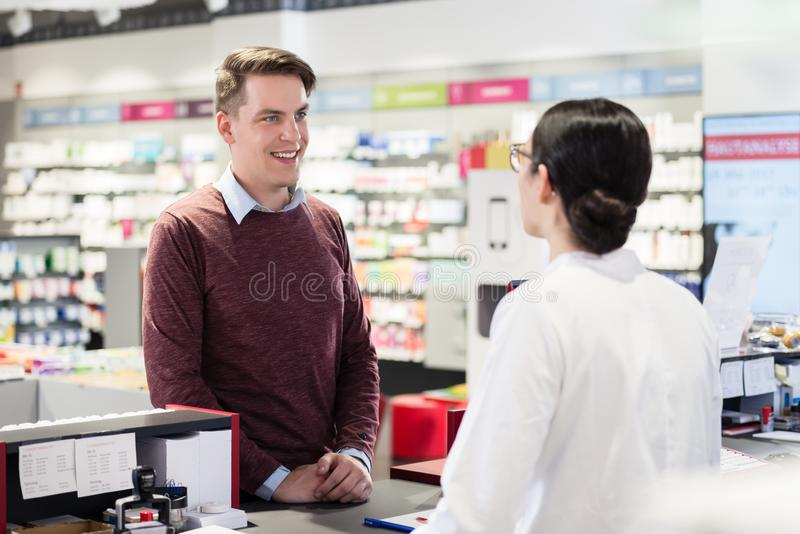 Happy customer listening to the recommendations of a reliable pharmacist stock photography