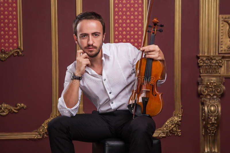 Portrait of handsome young musician playing the violin. Musical brutal unshaven man with beard and hendlebar with collar and chain on chest holding wooden stock photos