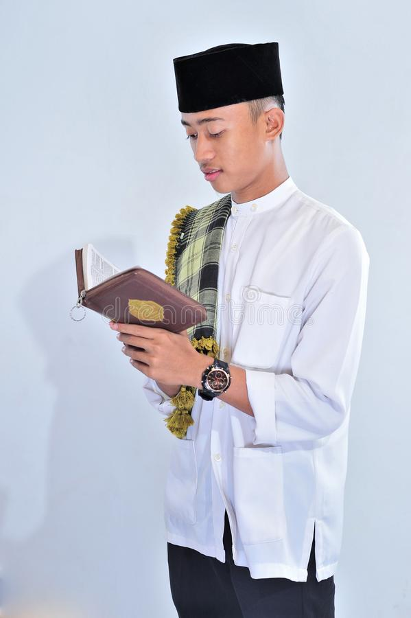 Portrait of handsome young muslim man enjoy reading tilawat ul quran a holy Quran in Ramadan stock image