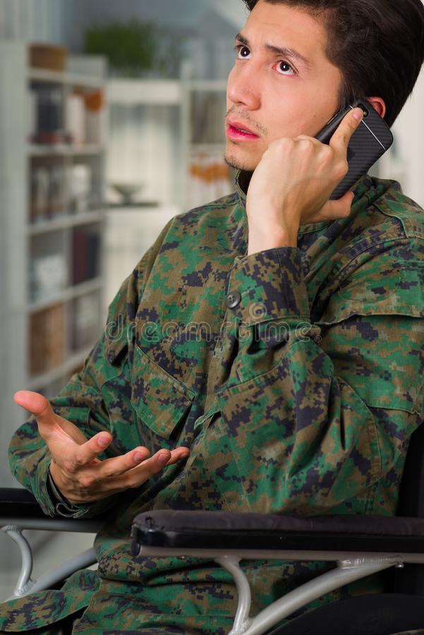 Portrait of a handsome young soldier sitting on wheel chair using his cellphone, in a blurred background.  royalty free stock photography