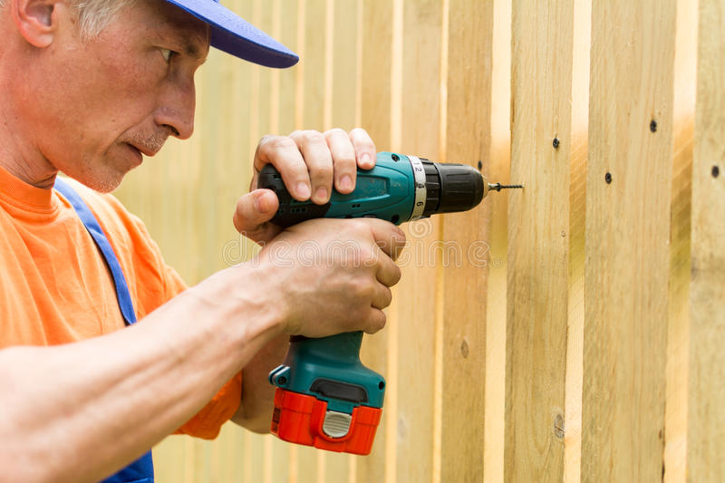 Portrait of a handyman, concentrating at work with a screwdriver stock photos
