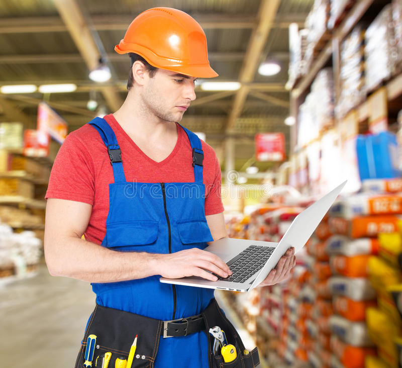 Portrait of handyman with laptop working warehouse royalty free stock photography