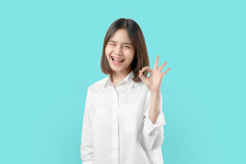 Portrait happily Asian woman shows ok sign and braces smiling witch looking at the camera on blue background. stock images